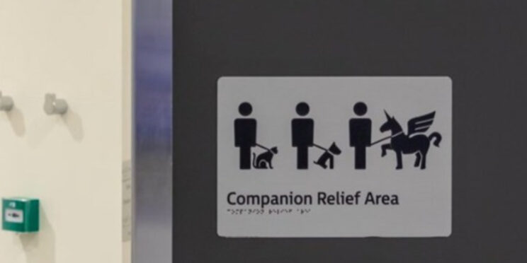 """A door sign at Sydney Airport entitled """"Companion Relief Area"""" with three people working a cat, koala and Pegasus supposedly on harness"""